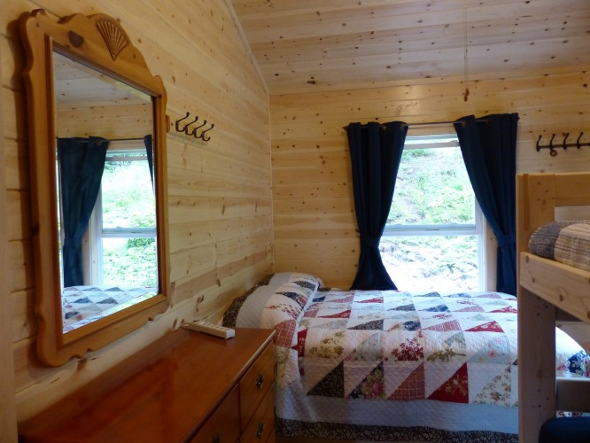 Second bedroom with dresser and mirror along with full bed and twin bunks.